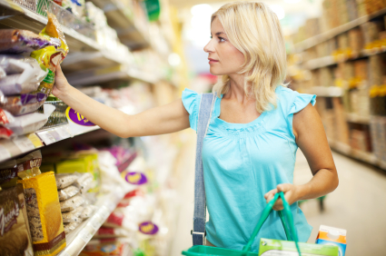 Blond attractive woman buying groceries in supermarket.