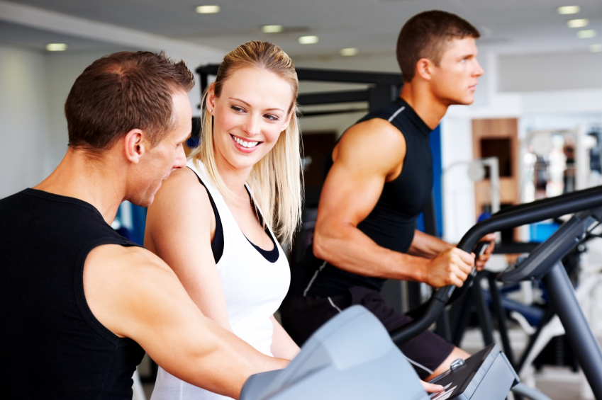 Personal trainer instructing woman at gym