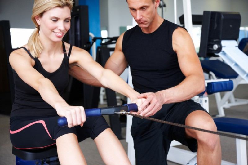 Trainer Helping a Woman on Rowing Machine