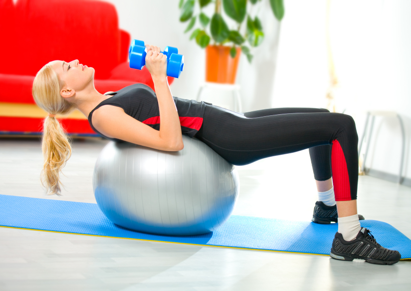 Woman doing fitness exercises with dumbbells and ball at home