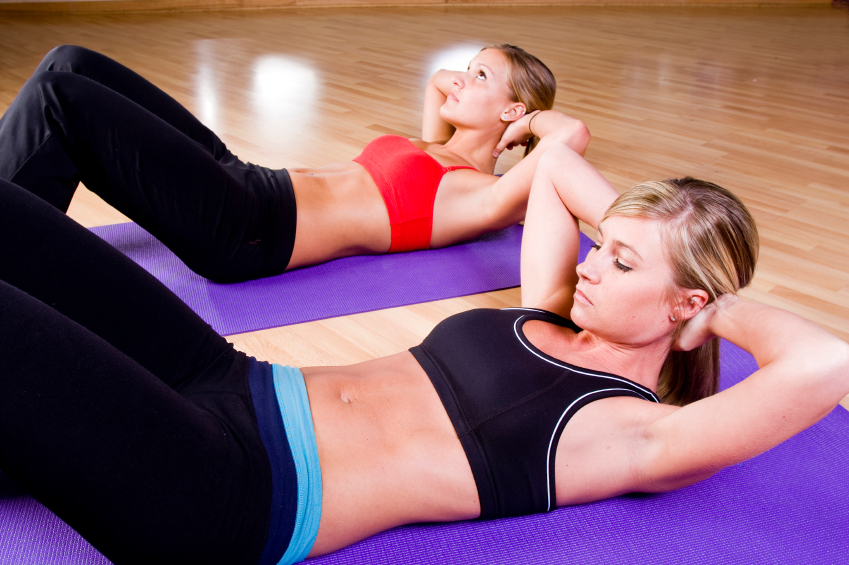 2 pretty girls doing sit-ups