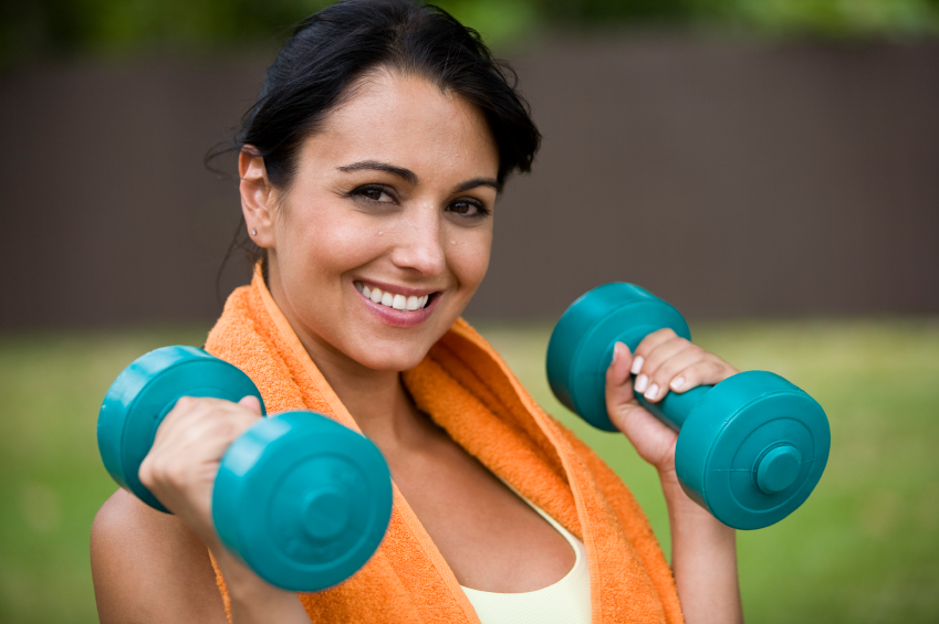 Young female holding dumbbells