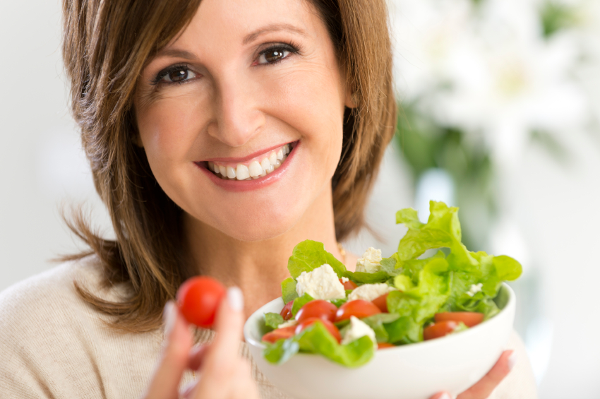 Happy mature woman holding a salad