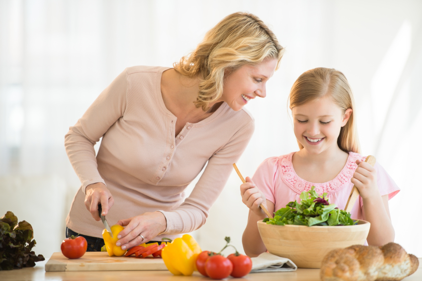 Girl Assisting Mother In Preparing Food At Counter