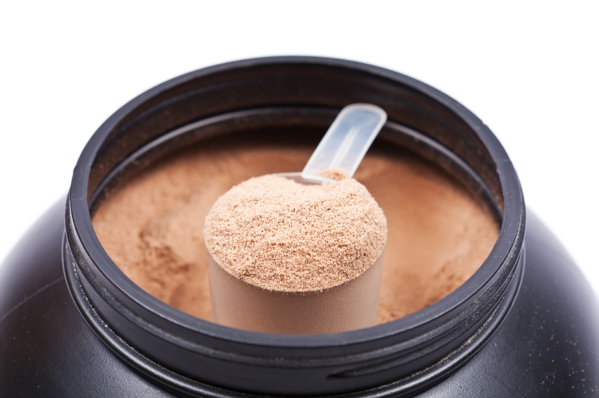Scoop of chocolate whey isolate protein in a black plastick cont
