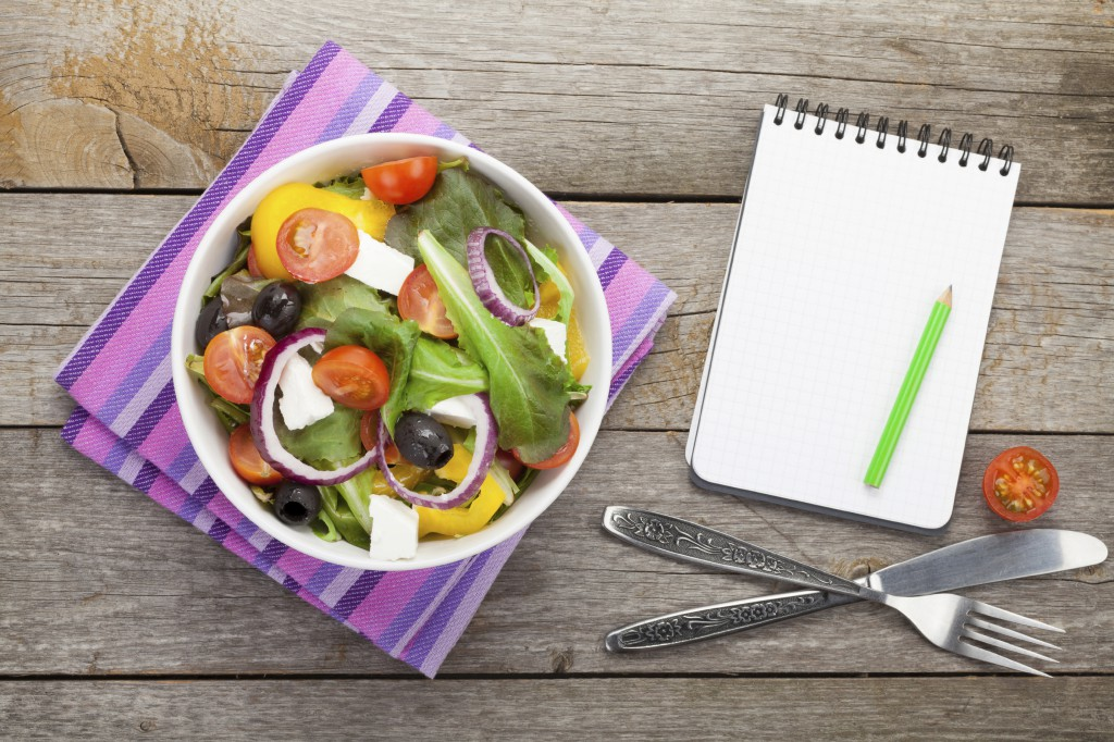 Fresh healthy salad and notepad for copy space