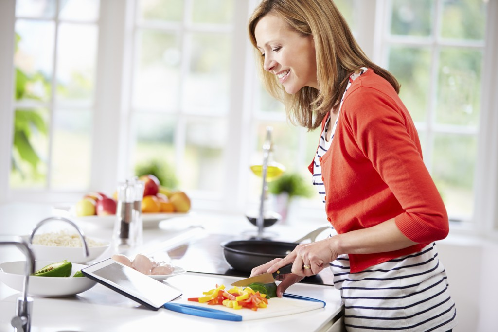 Woman In Kitchen Following Recipe On Digital Tablet