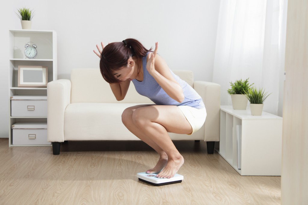 Upset woman on weigh scale at home, asian