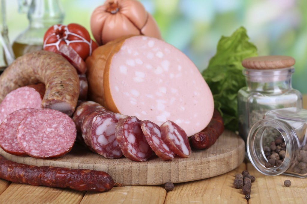 Different sausages on wooden table on natural background