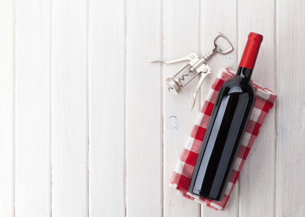 Red wine bottle and corkscrew on white wooden table background with copy space