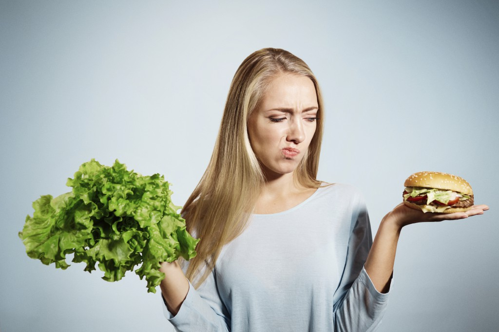 Pensive woman making decision between healthy food and fast food, over blue background
