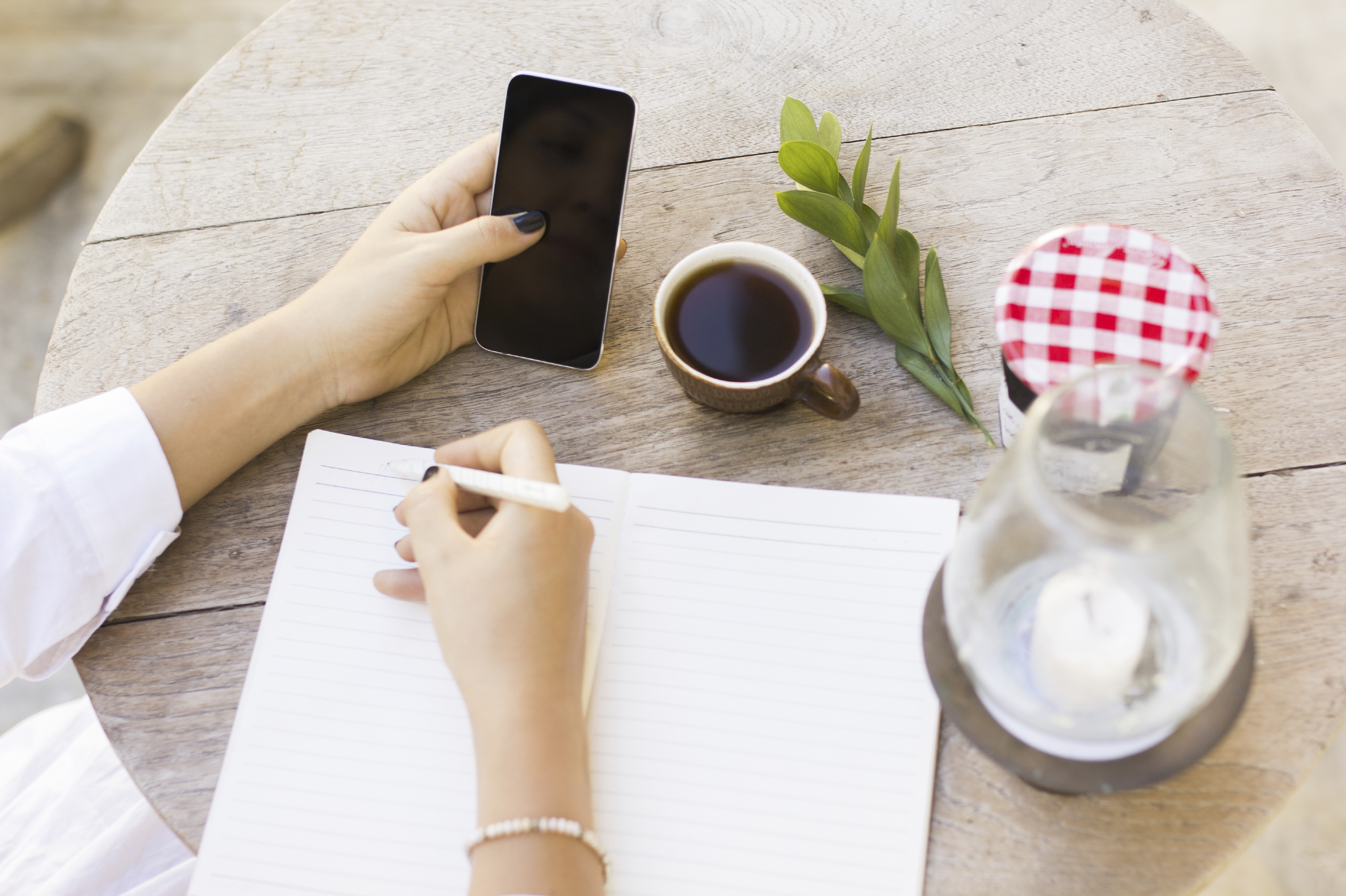 girl writes in notebook with cell phone and cup of coffee