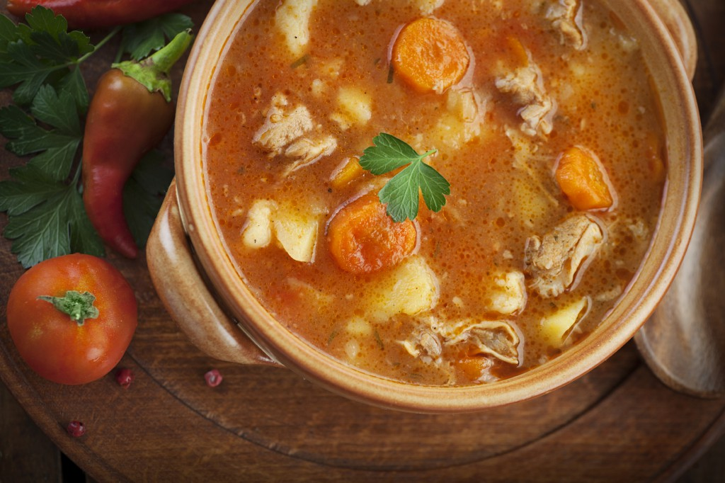 Delicious veal stew soup with meat and vegetables on wood.