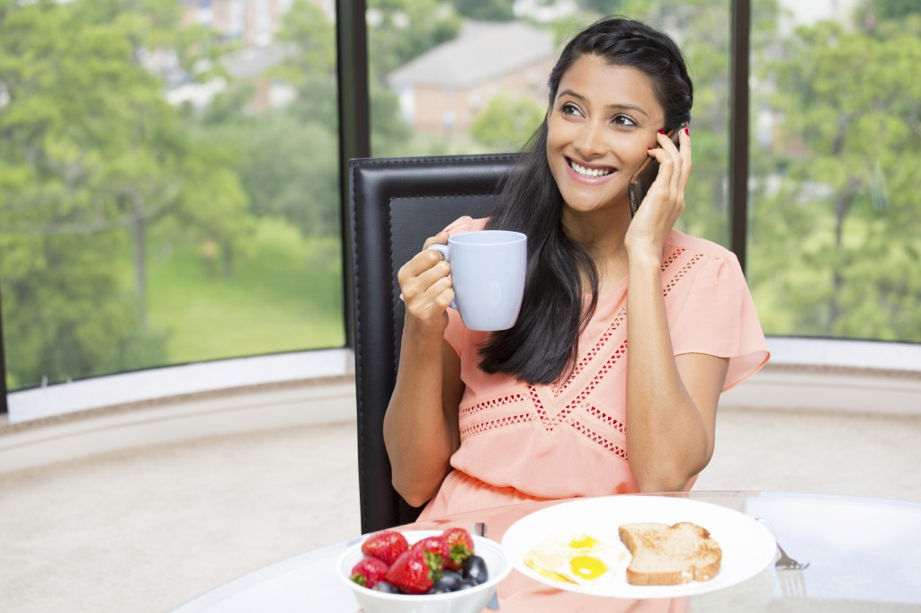 Closeup portrait of a young, attractive businesswoman, kick start day, health breakfast, fruit bowl, egg ,green tea, smiling, talking over the phone. Isolated glass window indoor greenery background.