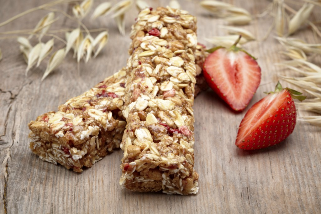 Granola bar and strawberries on wooden background