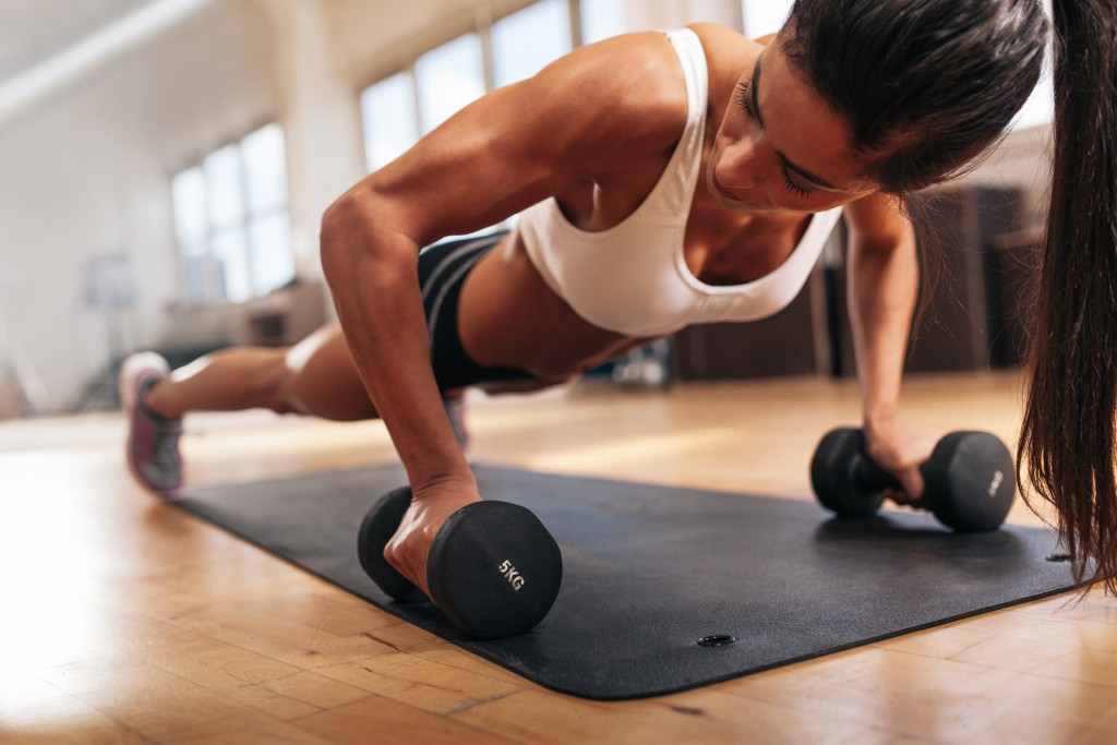 Gym woman doing push-up exercise with dumbbell. Strong female doing gym workout.