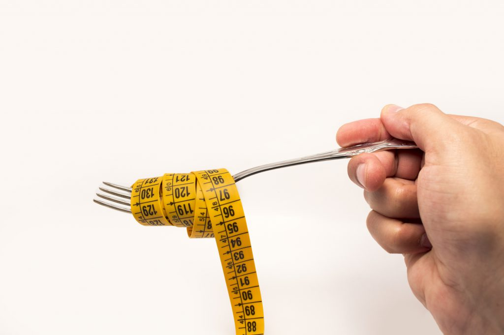 hand holding a fork with a tape measure for diet concept