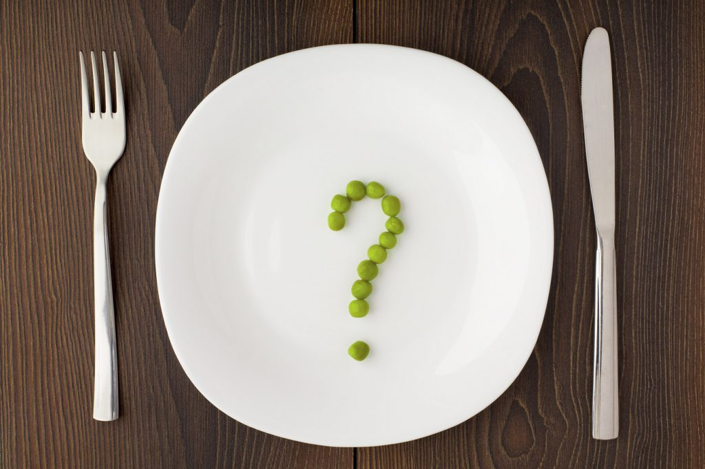 Question mark made of peas on a white plate