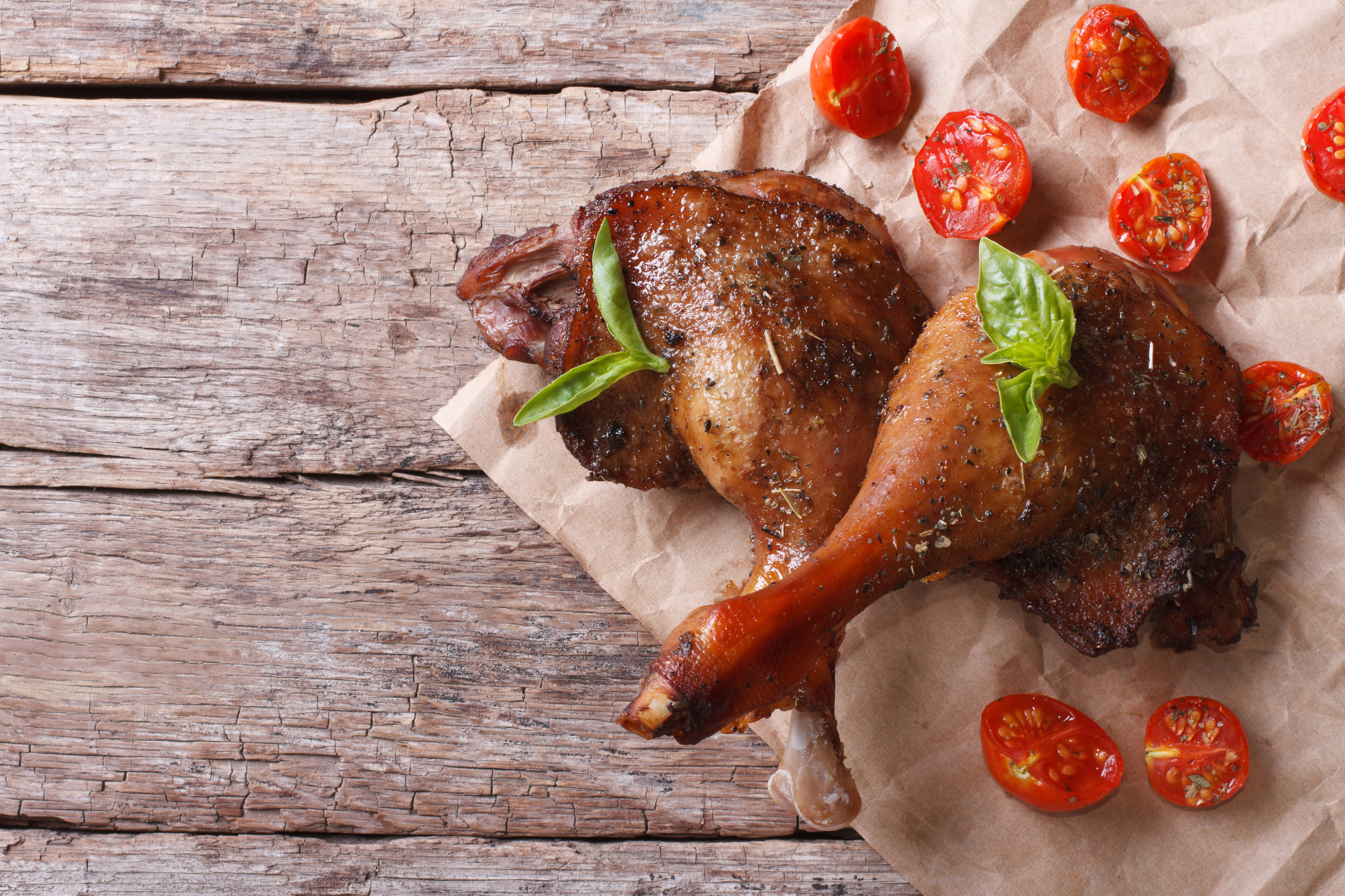 two roasted duck legs with basil and tomatoes close up on an old table top view horizontal
