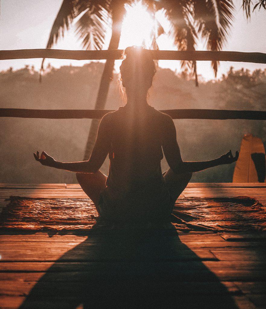 Femme en méditation sur un balcon au soleil