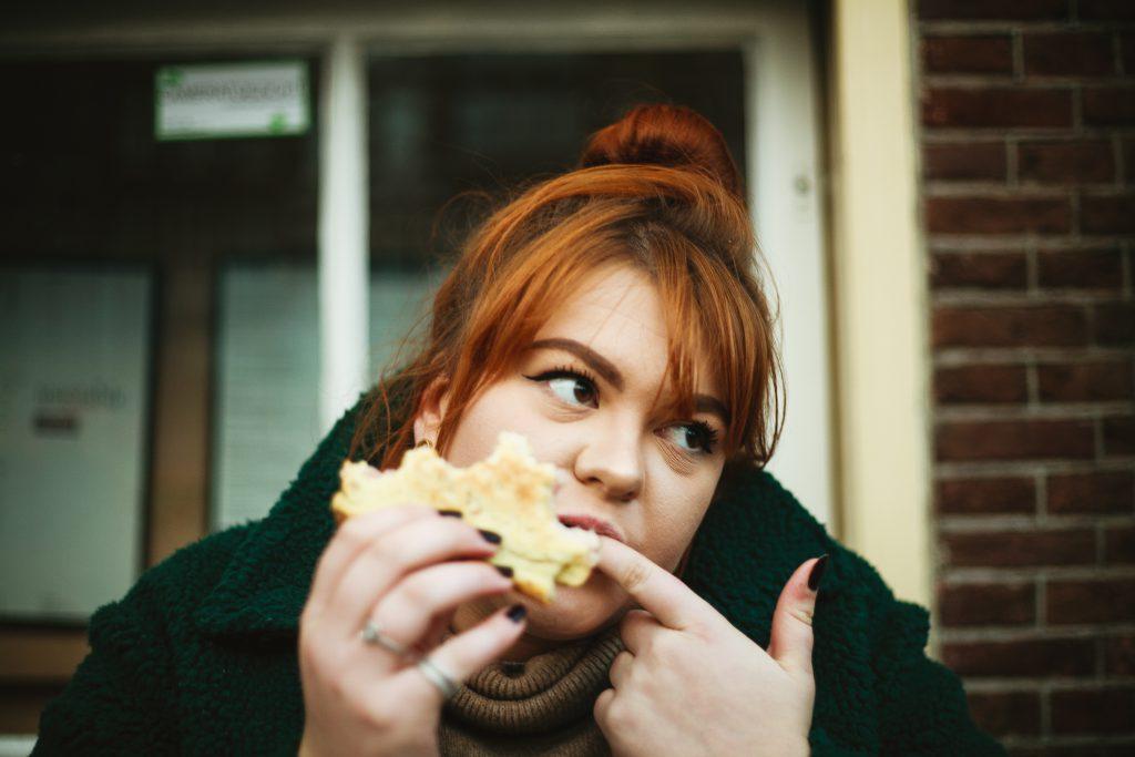 Une femme mange son sandwich sur sa galerie
